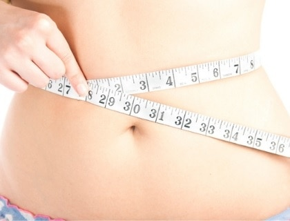 Woman measuring her belly with tape measure